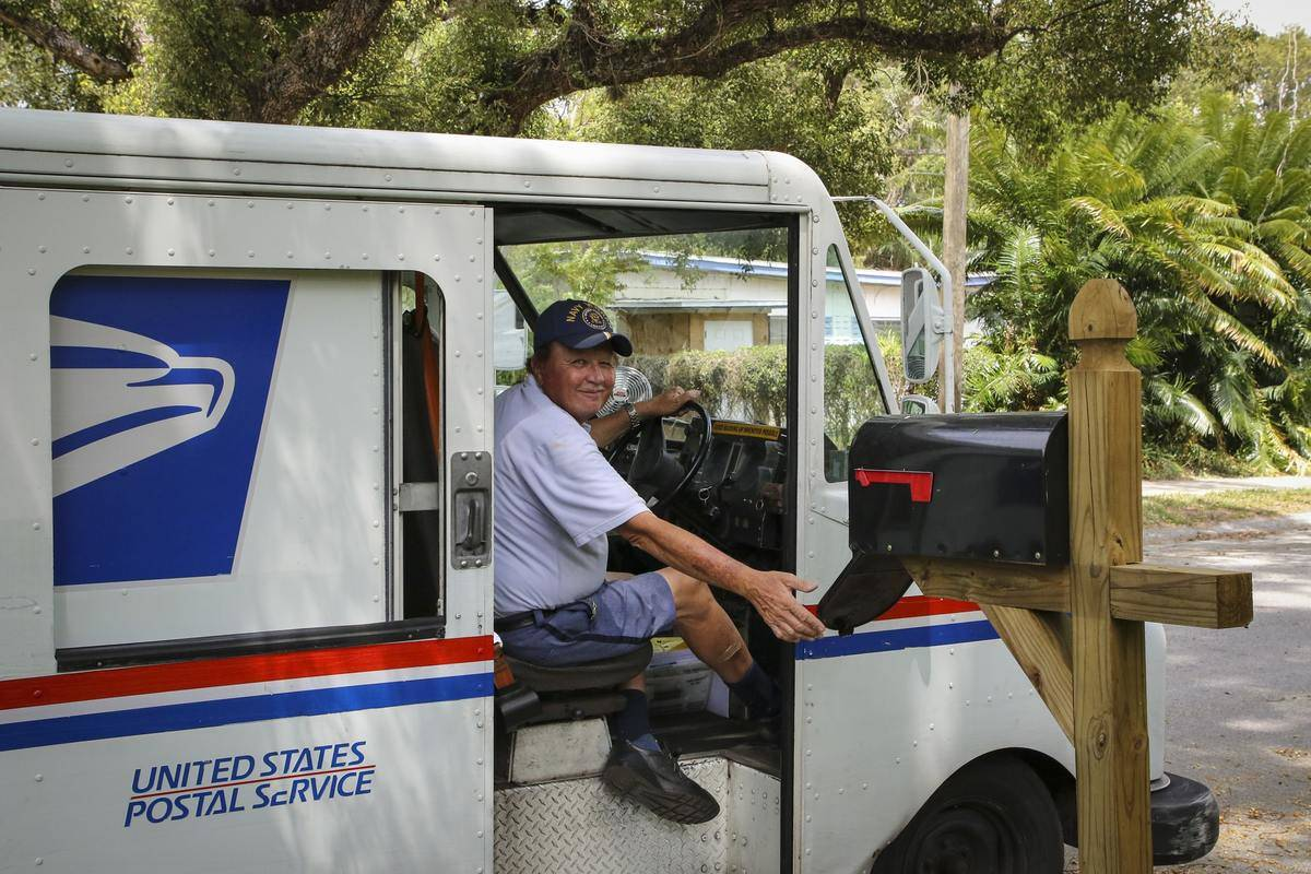 A postal worker smiles while checking a person's mailbox.