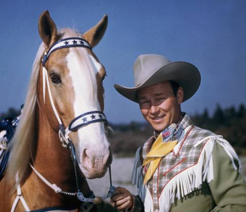 Roy Rogers stands with his horse, Trigger.